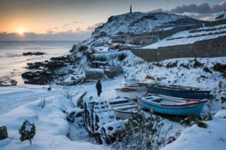 The sun sets as snow covers fishing boats left at Priest's Cove at Cape Cornwall near Penzance on 28 February