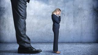 Piernas de hombre agrandadas ante mujer pequeña siendo intimidada