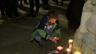 A boy lights a candle during the vigil