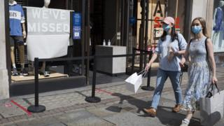 women in London walk by a levi's store