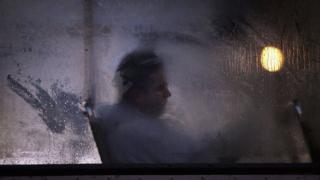 धुंधले शीशे के पीछे आदमी की तस्वीर