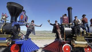 Men re-enact the historic Champagne Toast with the Jupiter (L) and the 119 steam engines meet on the railway line