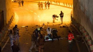 Un groupe de policiers encerclent le corps d'un suspect qu'ils ont abattu