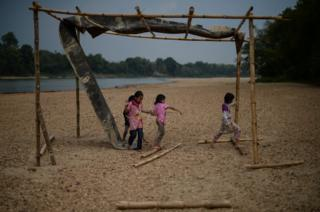 Children play along the dry banks of the Pahang river