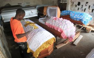 Manager Essau Thalley sews a sign of the Cross on a casket at the Creative Casket Center in Monrovia, Liberia, 02 November 2016. The Creative Casket Center was established by Boye Tugbeh in 2004, has nine employees