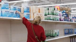 A woman reaches for toilet paper
