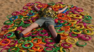 Boy lying on plastic ring toys