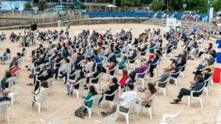 The audience maintains social distance during a performance on a beach in A Coruna, Spain, 4 July