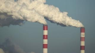 A coal plant with smoke rising into the air