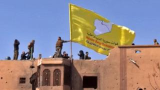 US-backed Syrian Democratic Forces (SDF) raising their flag atop a building in the Islamic State group's last stronghold in the eastern Syrian village of Baghuz, 23 March 2019