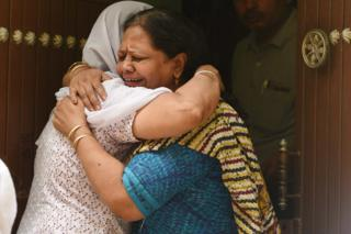Relatives mourn outside the house, where 11 members of a family were found dead in Delhi.