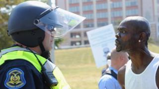 Un funcionario policial observa a un hombre que protesta contra el veredicto de no culpabilidad de un policía que mat'o a un menor en St. Louis, Missouri.