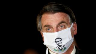 President Jair Bolsonaro speaks with journalists while wearing a protective face mask as he arrives at Alvorada Palace amid the coronavirus disease COVID-19 outbreak in Brasilia Brazil May 22 2020