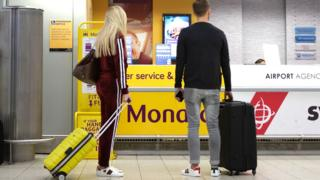 Passengers by Monarch desk at Luton airport