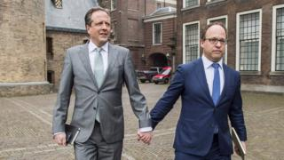 Politicians from Democrats 66 party, Alexander Pechtold (l) and Wouter Koolmees (r), held hands to show support for the movement