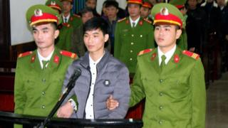 Activist Nguyen Van Hoa (C) standing trial at a local people's court in the central province of Ha Tinh, Vietnam