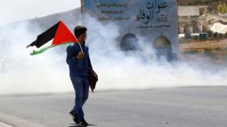 متظاهر يلوح بالعلم الفلسطيني خلال اشتباكات مع القوات الإسرائيلية قرب نابلس