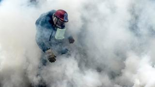 A demonstrator clashes with the riot police during a protest against Venezuelan President Nicolas Maduro, in Caracas