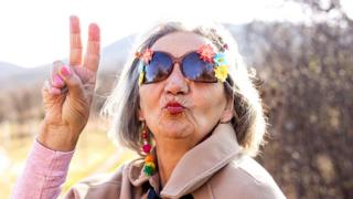 Elderly lady in sunglasses making a victory sign with her right hand and blowing a kiss
