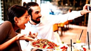 """Happy couple at a restaurant, taking a """"selfie"""" of themselves holding out a plate of food and smiling manically"""