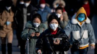 Travellers in Beijing all wearing facemasks