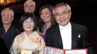 Japan's Ei-ichi Negishi (R) and his family display his Nobel diploma and medal after he received the shared Nobel Prize in Chemistry