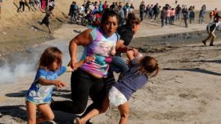 ہونڈورس سے تعلق رکھنے والی ایک پناہ گزین خاتون اپنی پانچ سالہ جوڑواں بچیوں کو آنسو گیس سے بچانے کے لیے بھاگ رہی ہیں۔