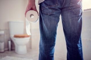 Hombre en un baño con rollo de papel en la mano