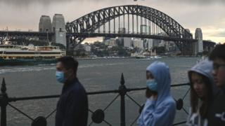 Personas enmascaradas caminan frente al puente del puerto de Sydney