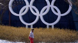 A volunteer walks past the Olympics Rings installation at the Olympic Village