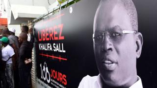 This file photo taken on July 31, 2017 shows a banner with a picture of Dakar's mayor Khalifa Sall, in jail awaiting trial for what supporters say are politically motivated embezzlement charges, on display in front of his offices in Dakar.