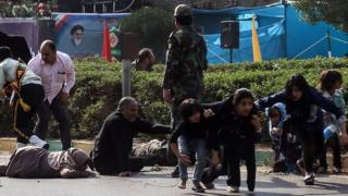 Iranian soldiers, women, and children lay down and run during the attack