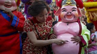 A woman puts money inside the belly bottom of a performer in pig costume during a performance to celebrate the Lunar New Year, or Spring Festival, in Chinatown