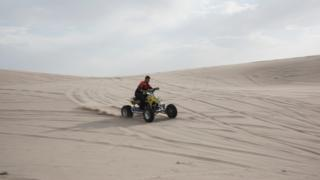 A man drives through the dunes on a quad bike