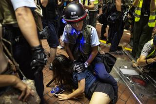 香港 防暴 警察 制服 一名 女 示威 者 / 7/7/2019)