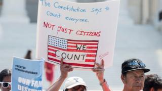 A protester calls for non-citizens to be counted