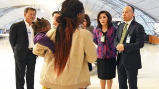 مسؤولون تايلانديون يتحدثون لفتاة من زيمبابوي
