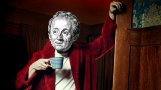 Una simulación de Denis Diderot con una bata roja y taza.