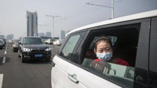 A girl sits in car while traffic stops during a silent tribute to those who died of coronavirus in Wuhan.