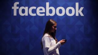 Una joven con un teléfono y con el cartel de Facebook de fondo.