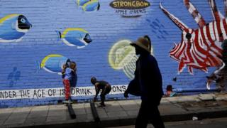A man walks past a new piece of graffiti art painted on a wall in downtown Johannesburg, South Africa, 07 December 2017. The art work, which depicts an underwater world with fish and a turtle, is in the Maboneng area of the biggest city in the country.