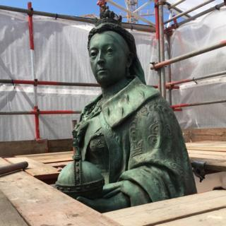 A statue of Queen Victoria with scaffolding