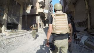 Figures walk through devastated street in Raqqa