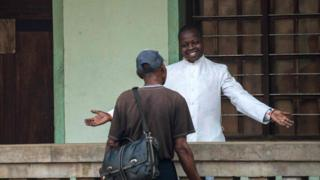 Father Lucien Ambunga, a Catholic priest who survived the Ebola virus, welcomes a faithful at the St Joseph Church in Itipo on June 11, 2018.