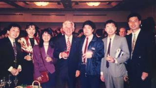 Bob Hawke smiles for a group photo with six Chinese students at a community dinner in Sydney in 1997