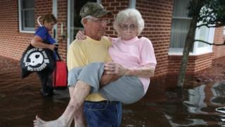 Bob Richling carries Iris Darden as water from the Little River starts to seep into her home in Spring Lake, North Carolina.