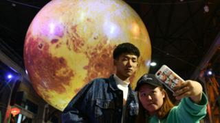 2018年中秋節前夕,中國民眾在一個月球狀的燈籠前拍照。
