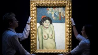 Employees of Sotheby's auction house pose for photographers with the 1901 painting La Gommeuse