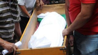 مصريون يحملون نعشا به جثمان