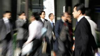 Japanese businessmen walk on a street in Tokyo' business district